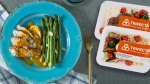 Packaged Trifecta Meal Plan next to a blue plate with asparagus with mustard chicken
