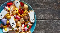 Bowl full of halloween candy on a wooden table