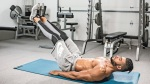 Fitness model working out his lower abs with lying leg raises exercise