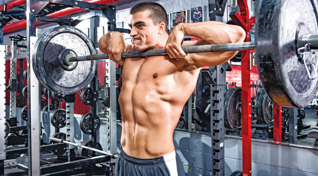 Bodybuilder doing shoulder workout with the upright row exercise