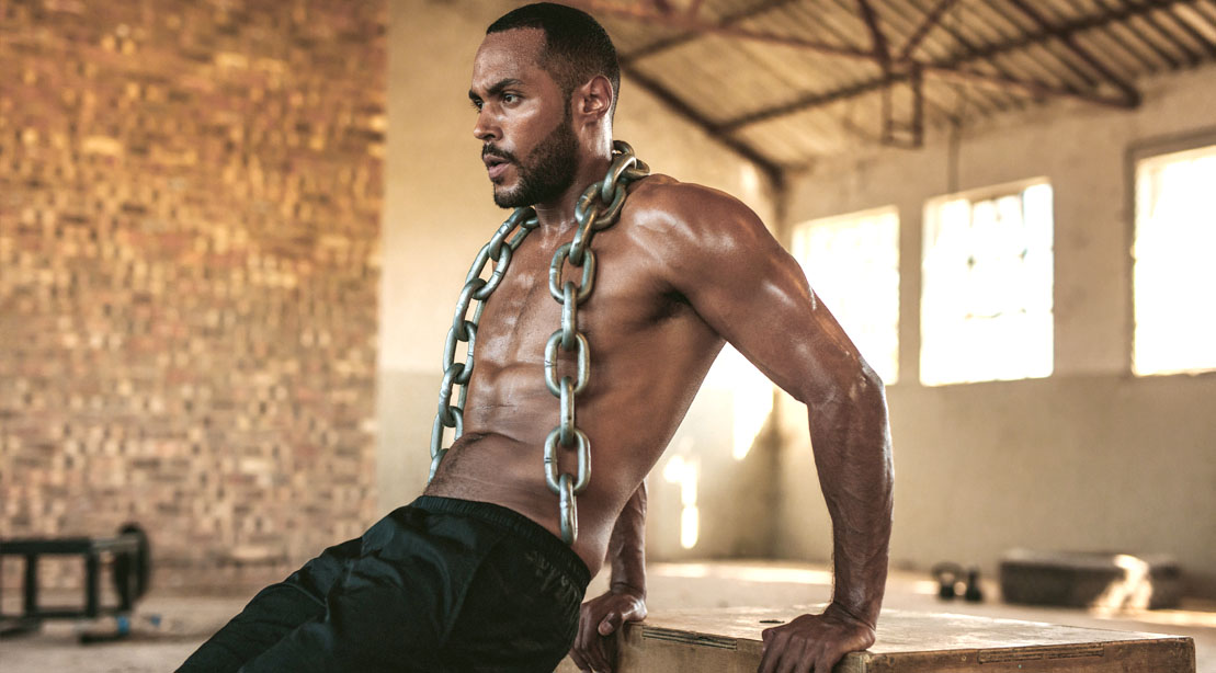 A muscular black man doing chest and arms workout with a weighted dip exercise