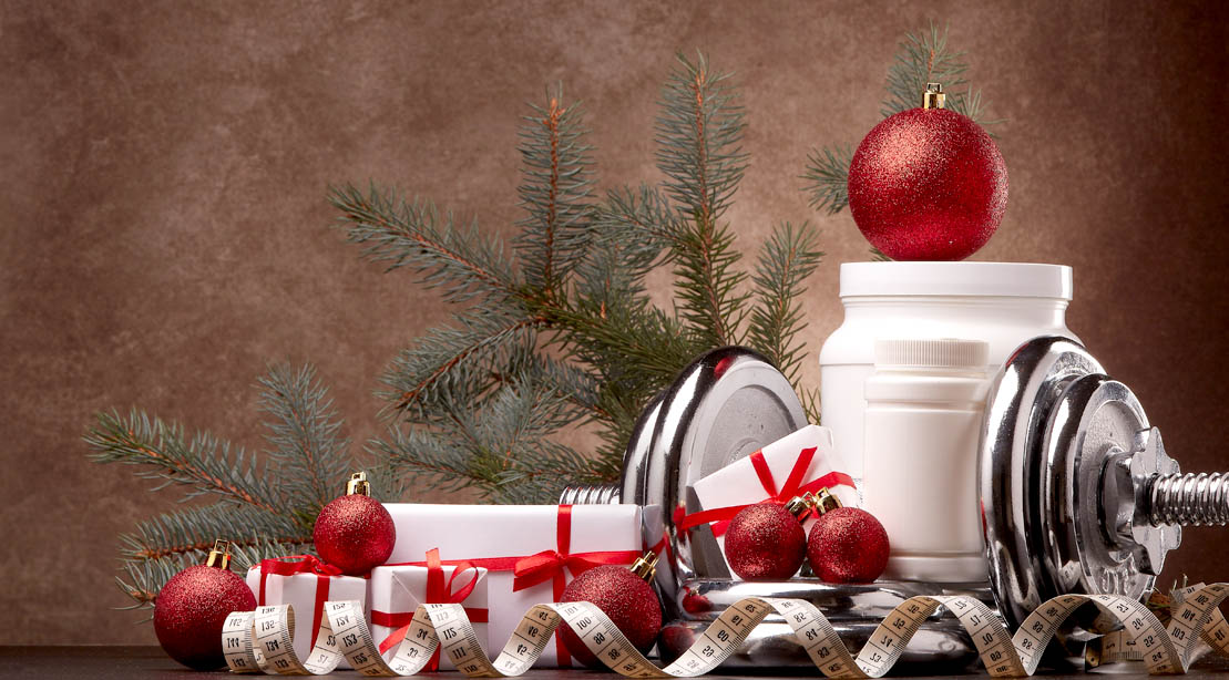 Chistmas-Holiday-Presents-and-Pine-Tree-With-Wrapped-Dumbbells-And-Supplements
