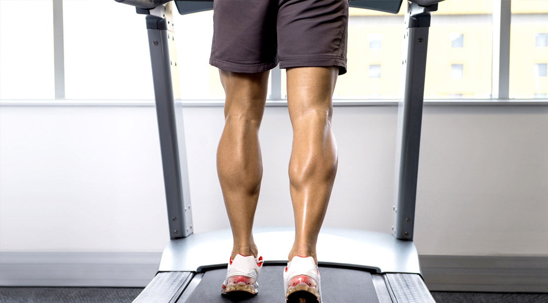 Fit muscular male with big calves muscle walking on a treadmill