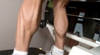 Fitness professional with big calves muscle working out his lower leg muscles with a calf raise exercise