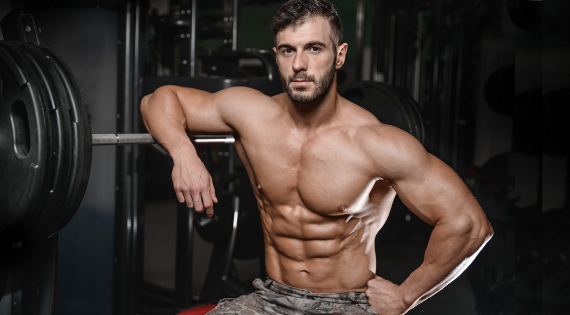 Bodybuilder sitting on a bench starting his abs workout