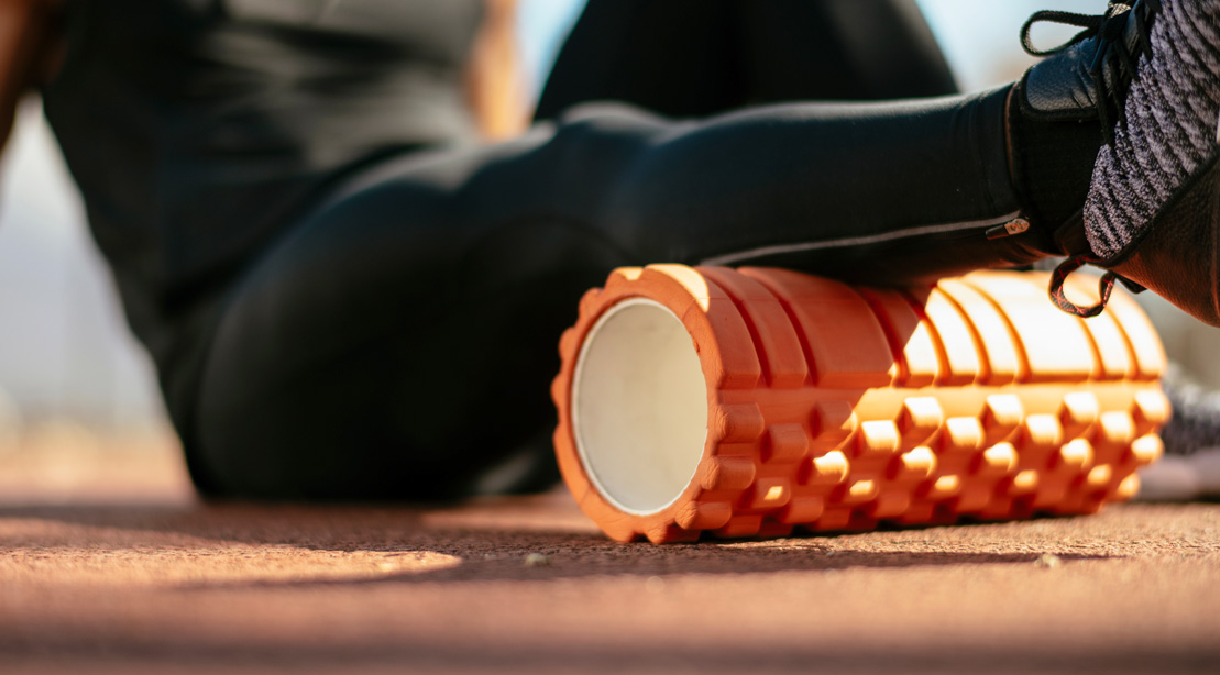 Athletic runner foam rolling his calf muscle on the track field