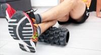 runner wearing sneakers while foam rolling his calves