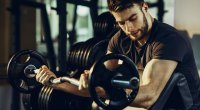 Bearded man working out his biceps and forearms with a preacher curl exercise
