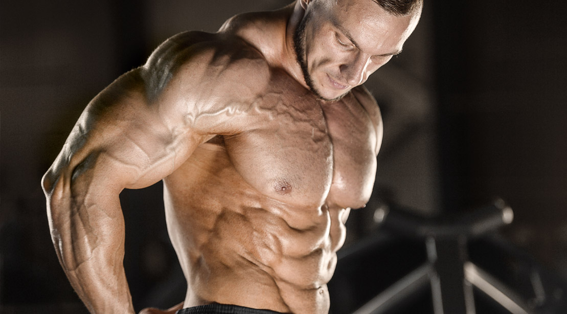 Muscular bodybuilder showing his shoulder muscles after his delts workout routine
