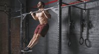 Muscular-Fit-Man-Working-Out-Without-A-Shirt-Doing-Plyometric-Pull-Ups