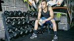 man resting in gym by dumbbell rack
