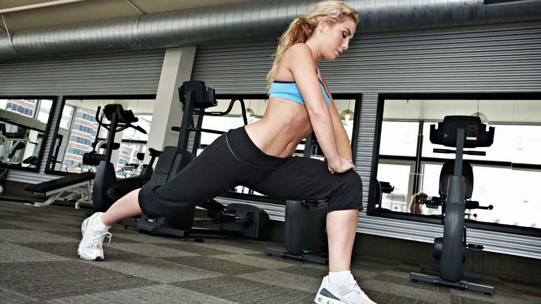 woman stretching her legs in gym