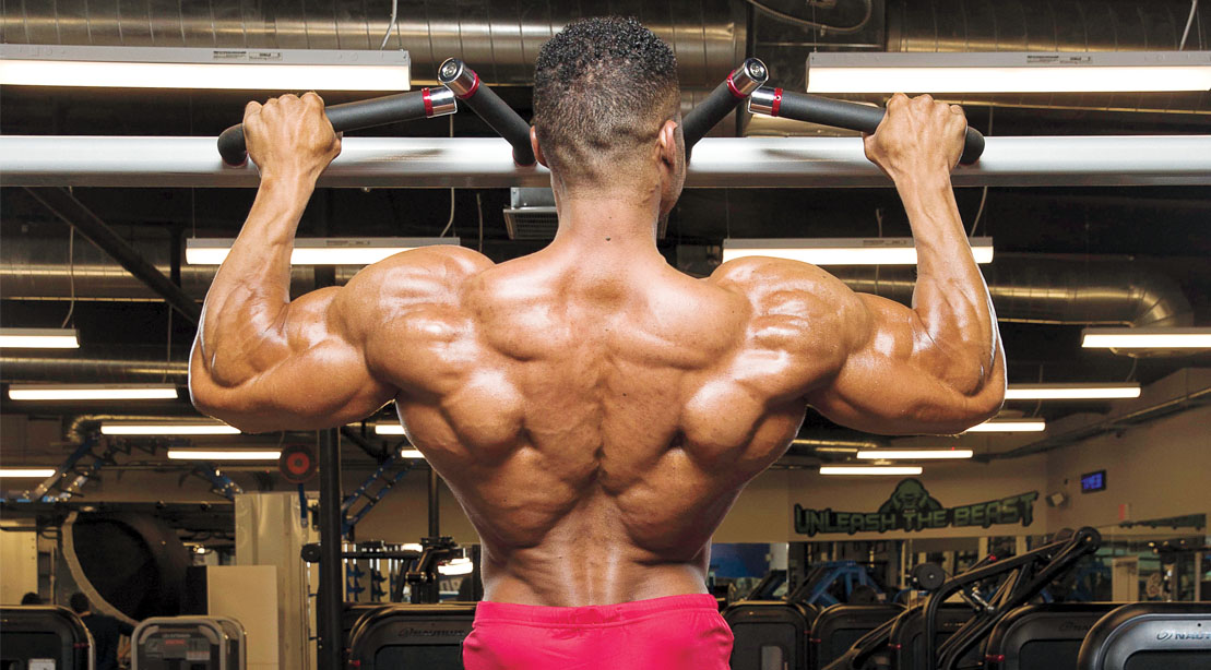 Professional bodybuilder Henry Pierre Ano doing a back workout using a V-Bar pullup lat exercise