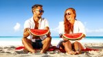 A happy fit couple eating watermelon on the beach