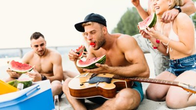 Muscular man eating a watermelon on the beach with his friends