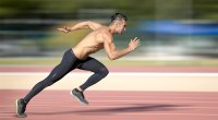 Muscular man doing HIIT sprinting workouts by sprinting on a running track