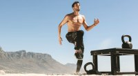 Physically fit man doing exercises on the beach with a kettlebell and high knee exercise