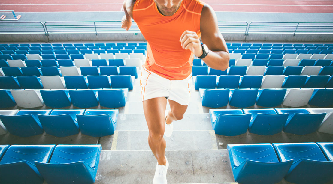 Physically fit man doing a cardio HIIT workout by running up a flight of stairs