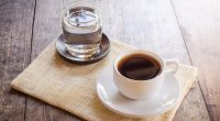 A glass of water and coffee on a burlap tablecloth