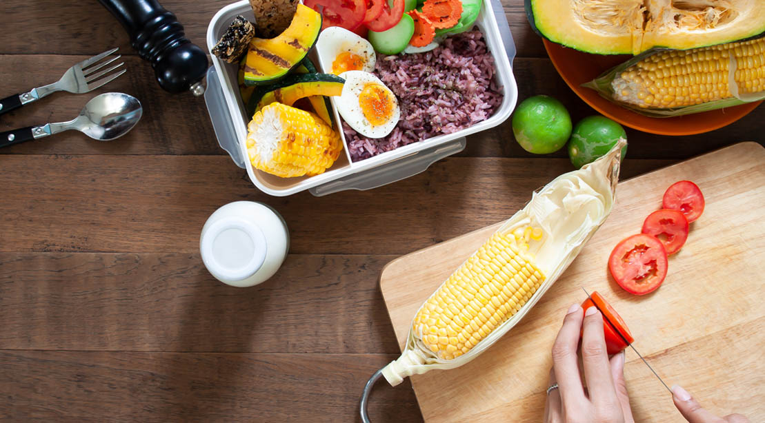 Person preparing vegetables on a cutting board for a clean bulk meal plan