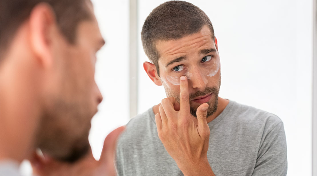 Man applying lotion to his skin and looking in the mirror