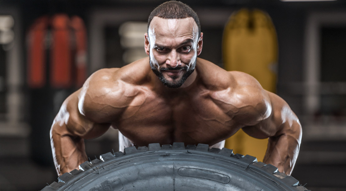 Bodybuilder raising his eyebrow and working out his trap muscles working out with tire flip exercise