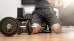 Man wrapping his hands for a home workout with dumbbells