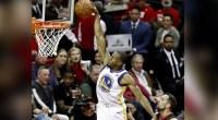 Golden State Warrior player Andre Igoudala dunking a basketball in an NBA basketball game