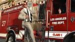 Dwayne Johnson hangs off the side of a fire truck.