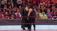 The Undertaker stares down Roman Reigns.