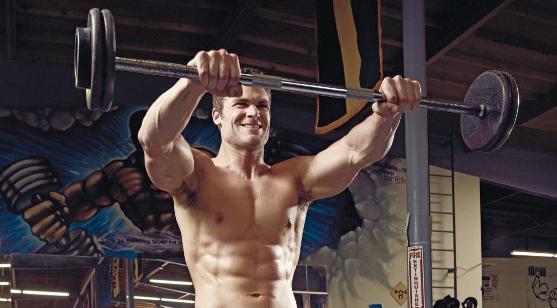 Man doing shoulder exercise: barbell front raise