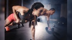 Man And Woman Doing Plank Rows With Dumbbells