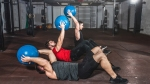 Group of three men working out in the gym performing weighted crunches exercise with a medicine ball