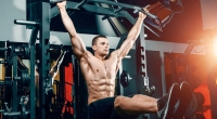 Man working out his lower abs with hanging leg raise exercise