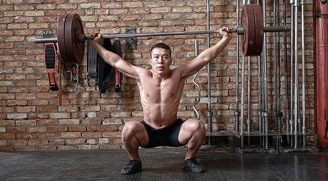 Man Does Barbell Squat Snatch Exercise