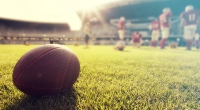 Close-Up Of Football Lying On Field Next To Football Players