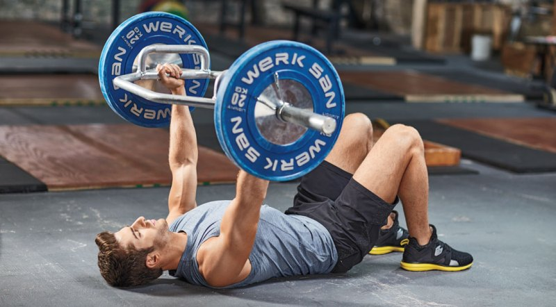Physical fit man working out the chest with a trap bar floor press