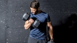 Bodybuilder doing a workout for biceps with dumbbell curls exercise