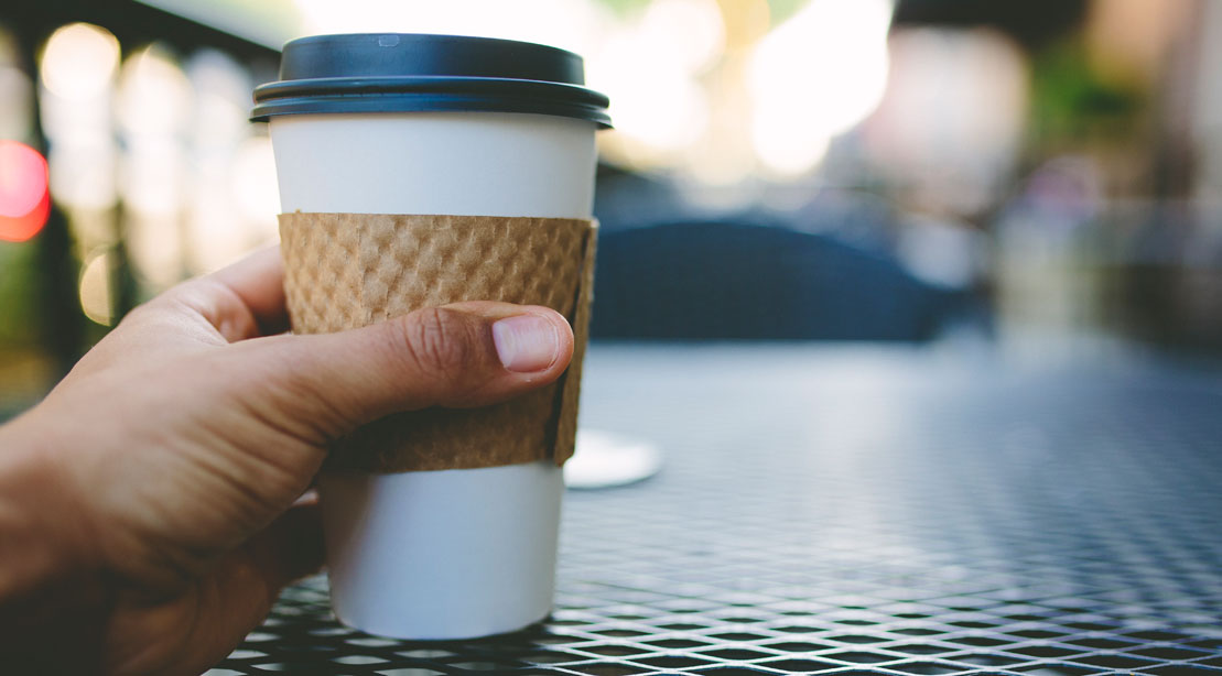 Man's hand holding a cup of coffee in a to-go cup