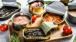 A Variety Of Canned Fish Displayed On A Cutting Board