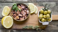 Healthy-Canned-Octopus-On-A-Wooden-Board-with-Olive-And-Lemon