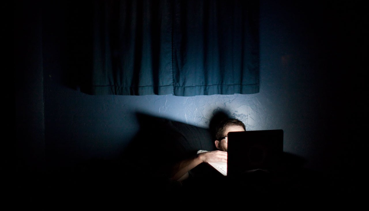 Man on laptop in bed in the dark