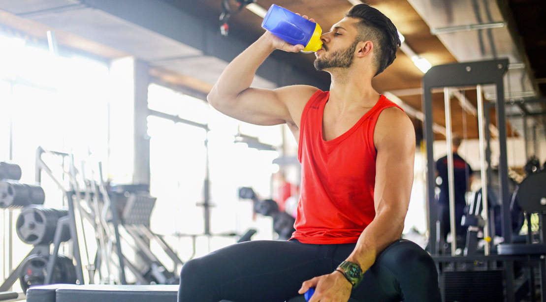 Man drinking protein shake in the gym