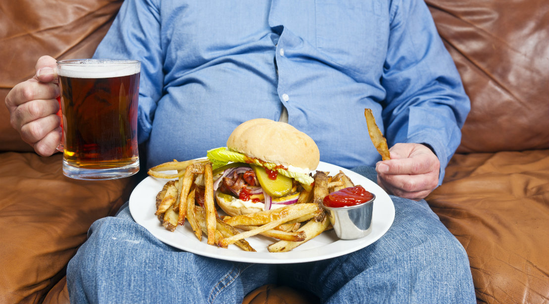 Seated Man With Plate of Food and Beer