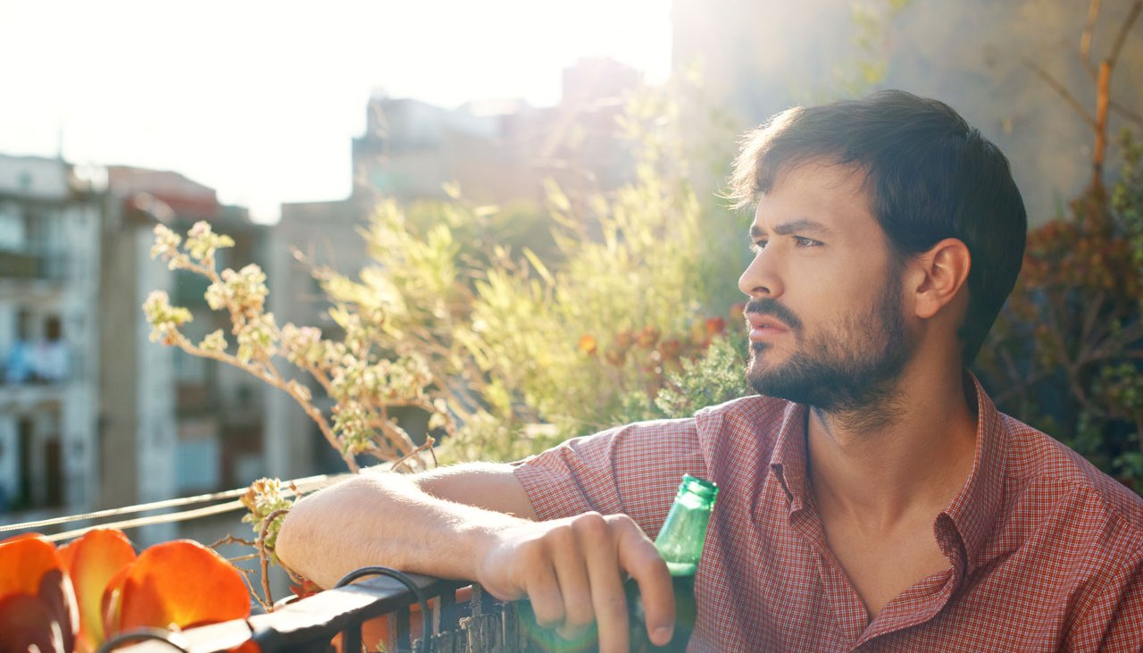 Man drinking beer on balcony