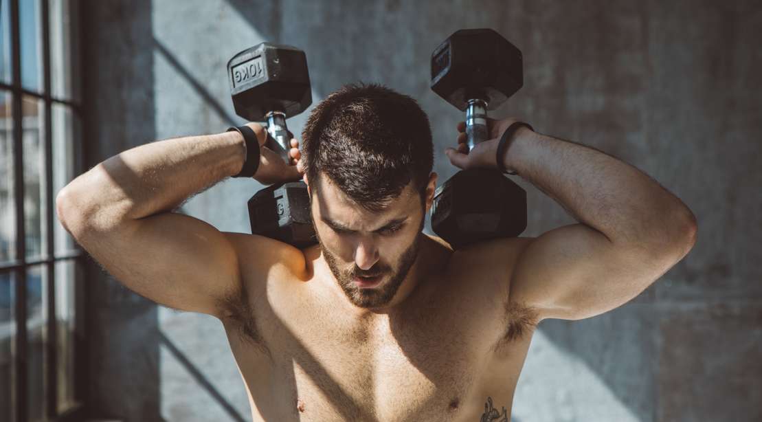 Muscular man and bodybuilder working out his chest with a dumbbell chest workout