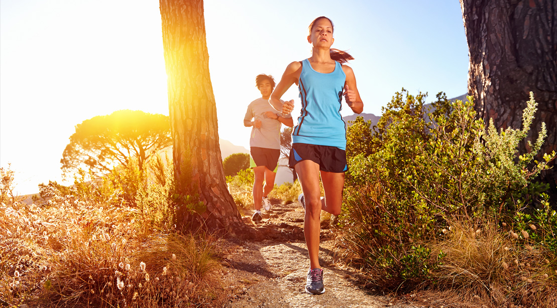 Female running down a mountain trail and training for a marathon and stronger mental health