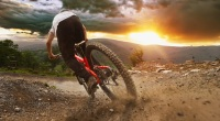 Mountain biker riding down a dirt trail during sunset