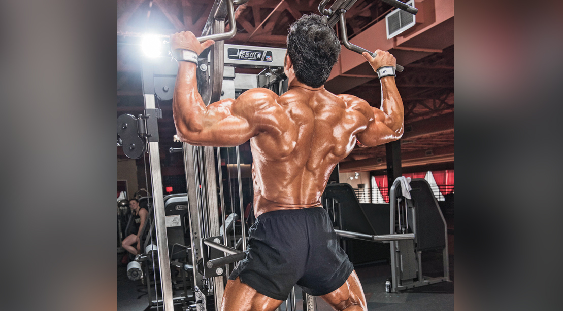 Muscular bodybuilder doing a back workout using the back exercise the pullup