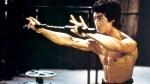 Martial artist and kung fu legend Bruce Lee holding up Nunchucks